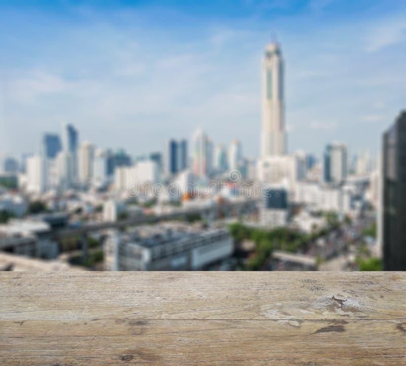 Houten lijstbovenkant met vage abstracte de stad in achtergrond van Bangkok stock fotografie