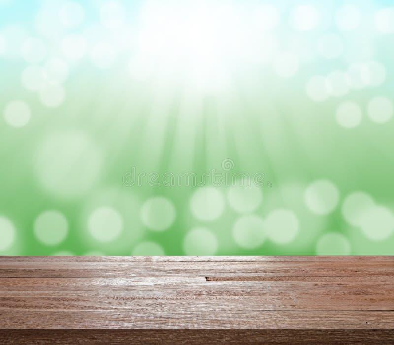 Houten lijstbovenkant op groene vage bokeh licht en zonstraal stock afbeelding