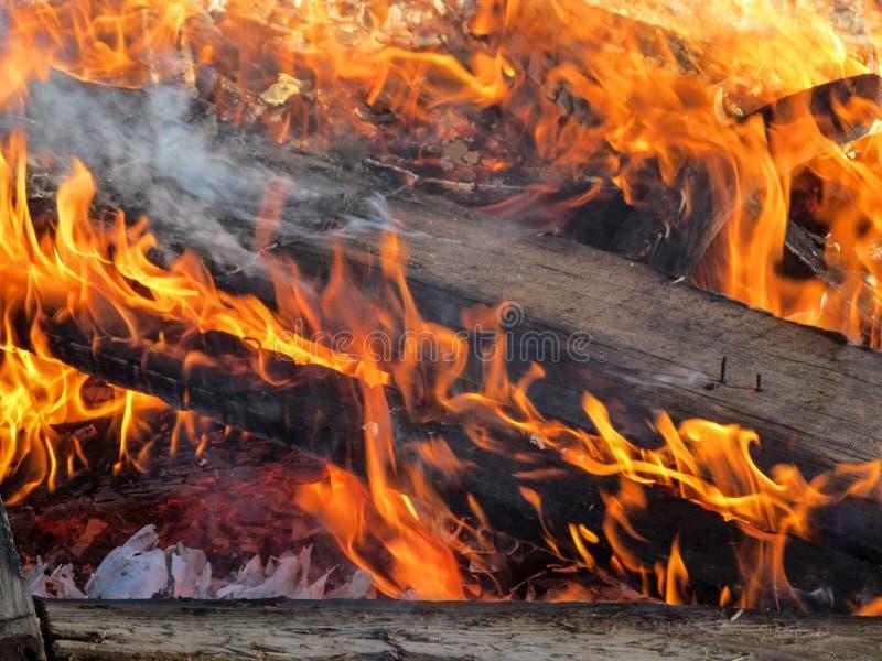 Houten logboekenbrandwond in een oranje vlam met rook royalty-vrije stock afbeelding