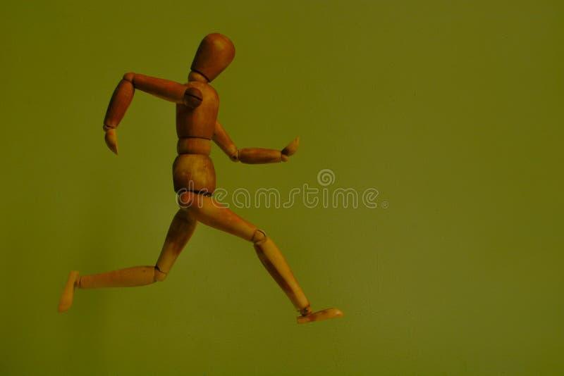 Houten lopende mens voor een exotische groene muur royalty-vrije stock afbeeldingen