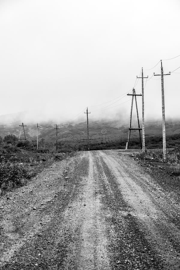 Houten machtslijnen dichtbij landweg in de bergen van Kamchatka Het Schiereiland van Rusland, Kamchatka Zwart-wit beeld stock foto