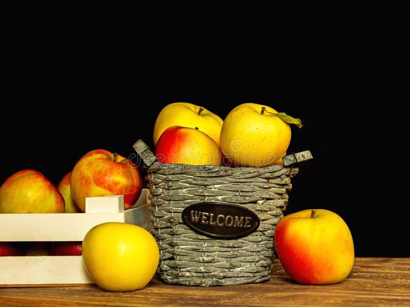 Houten mand en krat met verse kleurrijke appelen op donkere achtergrond royalty-vrije stock fotografie
