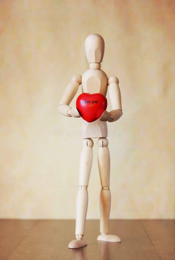 Houten marionet die een rood hart in zijn handen houden Conceptueel beeld royalty-vrije stock foto's