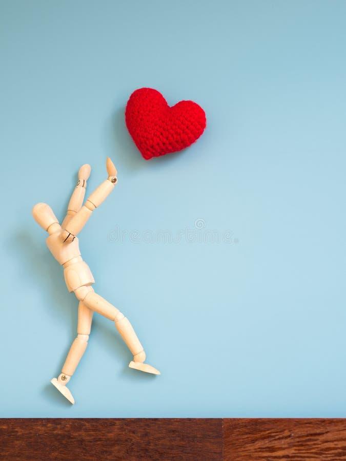 Houten marionet die van de houten vloer in de lucht springen om het rode hart te vangen drijvend in de hemel De houten marionet p royalty-vrije stock afbeeldingen