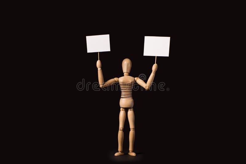 Houten marionet met een affiche of banner in hun handen op een zwarte stock fotografie
