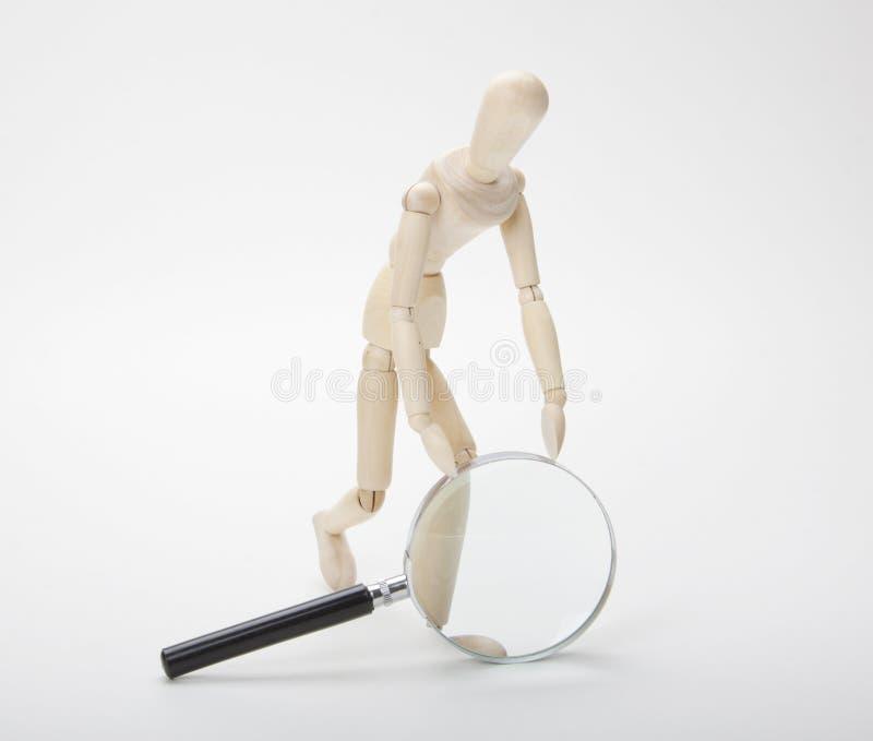 Houten mens met vergrootglas stock afbeeldingen