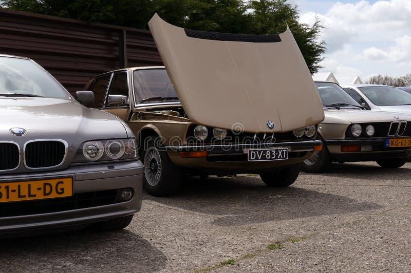 Хаутен, Нидерланды-19 апреля 2014 года: Золотой BMW E24 на выставке с открытым капотом во время автосалона. Публичное мероприятие без билетов. С другой стороны стоковое изображение