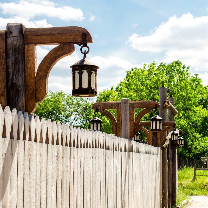 Houten omheining en een rij van antieke lantaarns langs het Tegen stock afbeelding