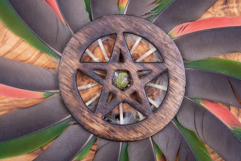 Houten omringd die Pentagram-symbool met Unakite-steen in het midden van een cirkel van kleurrijke papegaaiveren wordt gemaakt Vi royalty-vrije stock afbeelding