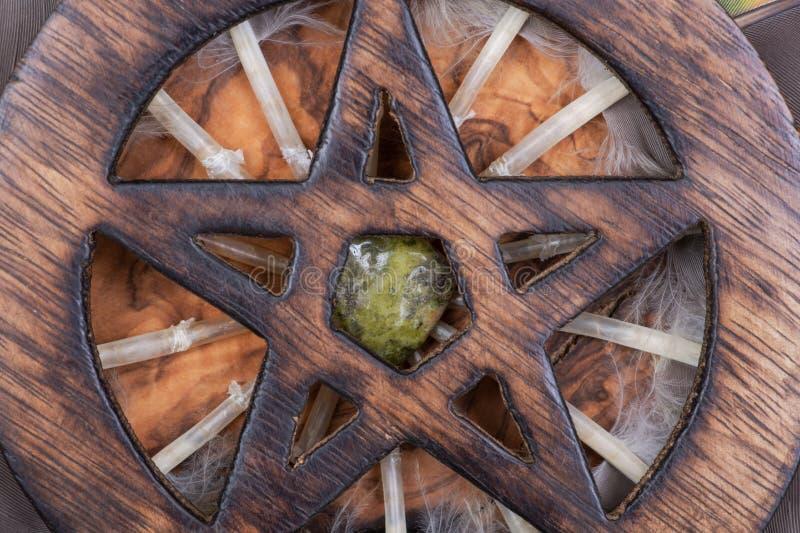 Houten omringd die Pentagram-symbool met Unakite-steen in het midden van een cirkel van kleurrijke papegaaiveren wordt gemaakt Vi stock fotografie