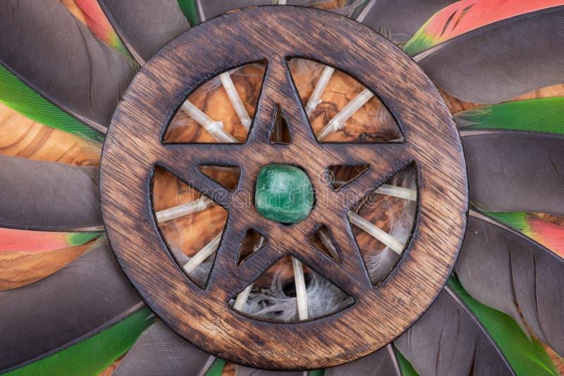 Houten omringd Pentagram-symbool met Groene die Aventurine in het midden van een cirkel van kleurrijke papegaaiveren wordt gemaak stock fotografie