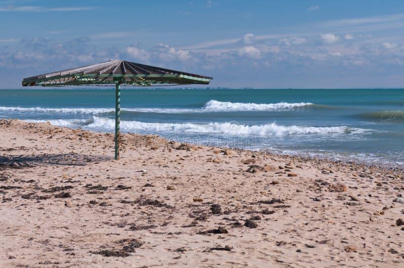 Houten paraplu op leeg strand stock afbeelding