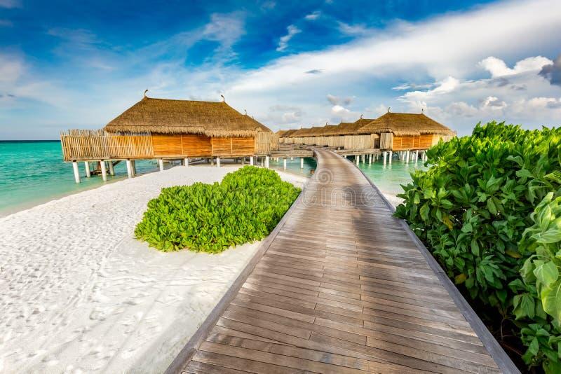Houten pier en cabines op de Maldiven stock afbeelding