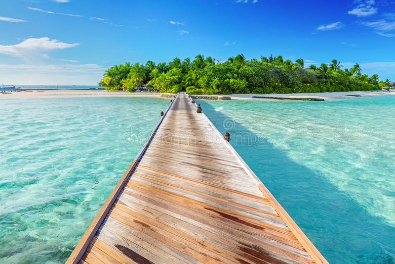 Houten pier naar een klein eiland in de Maldiven royalty-vrije stock afbeelding