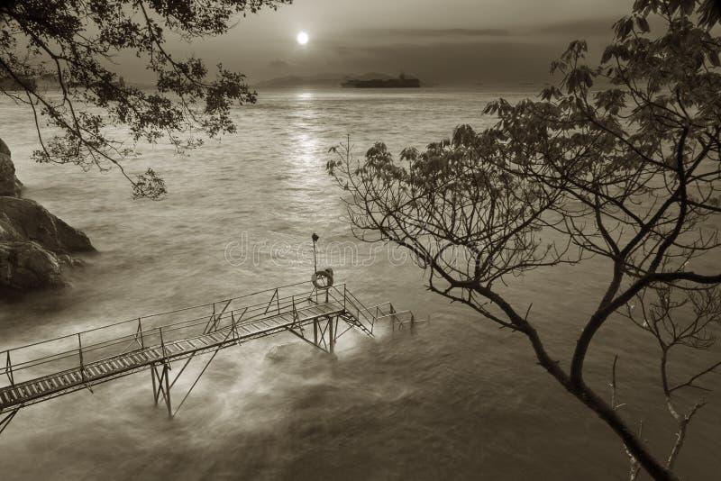 Houten pier onder zonsondergang stock foto's