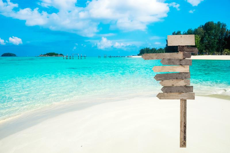 Houten pijlenuithangbord op mooie tropische overzees stock fotografie