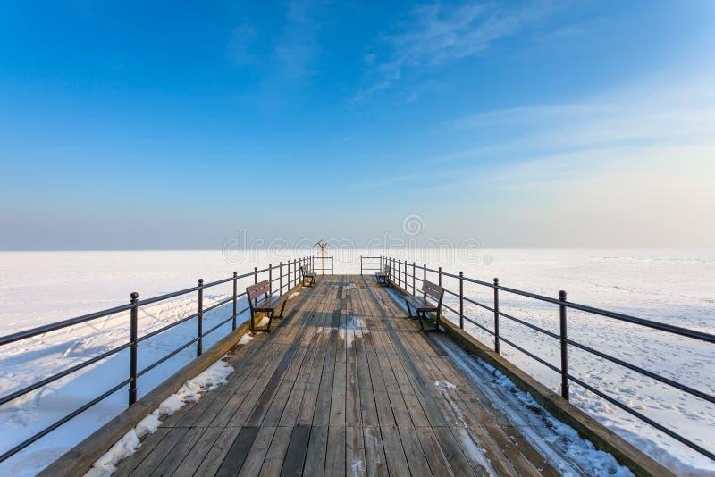 Houten pijler op het bevroren overzees stock foto's