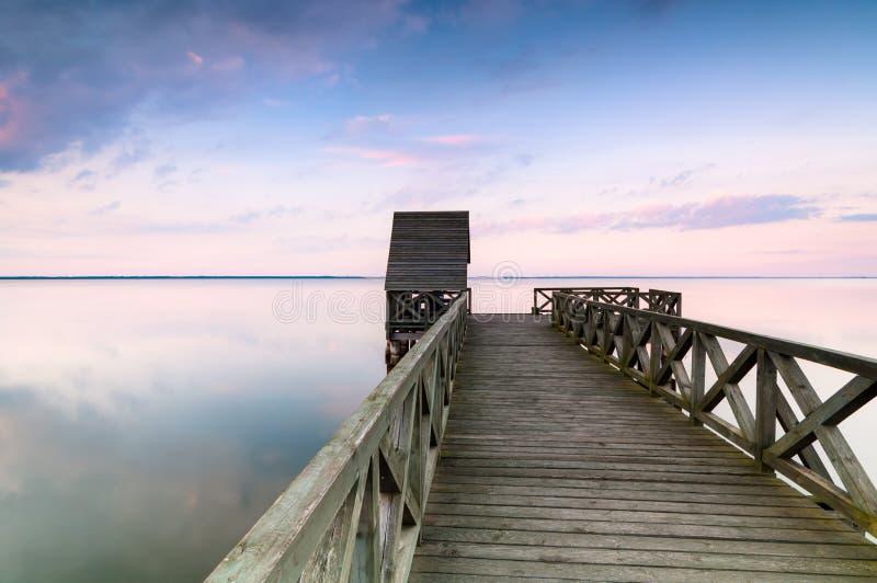 Houten pijler op kalm meer bij zonsondergang stock fotografie