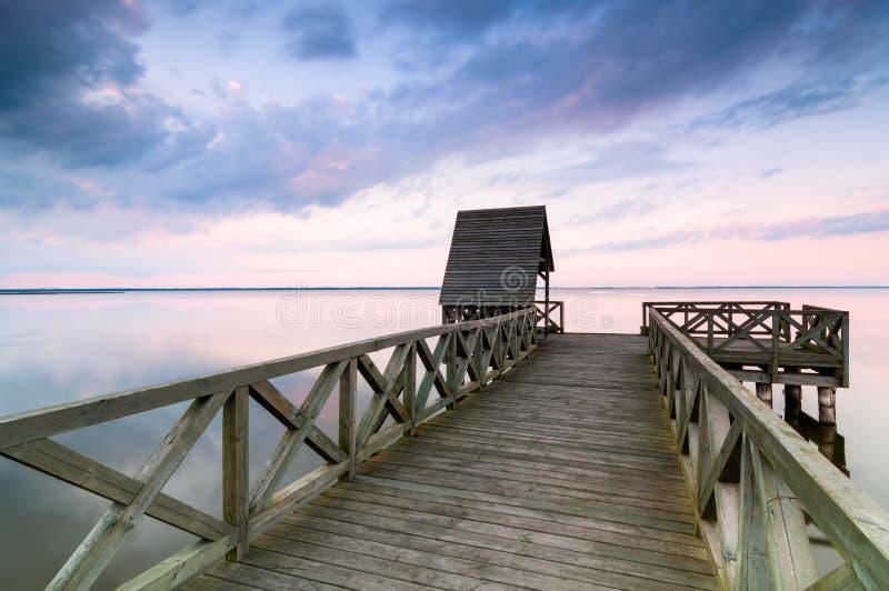Houten pijler op kalm meer bij zonsondergang stock foto's