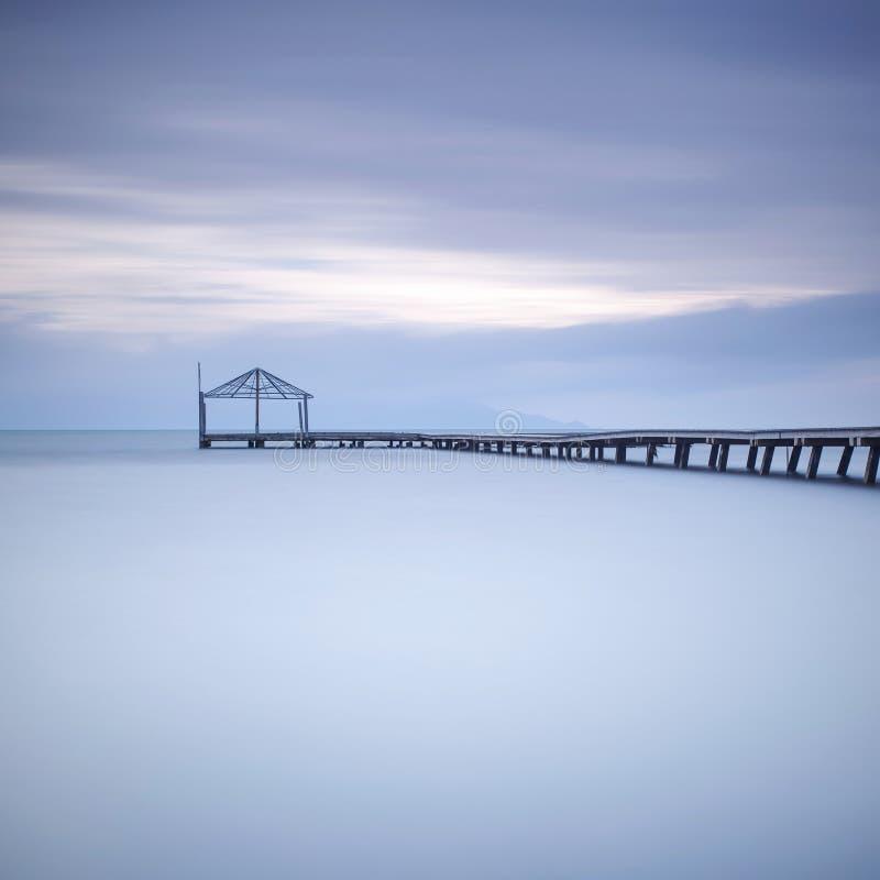 Houten pijler of piersilhouet en blauwe oceaan op zonsondergang stock afbeeldingen