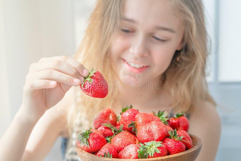 Houten plaat met aardbeien in meisjeshand op lichte achtergrond stock afbeeldingen