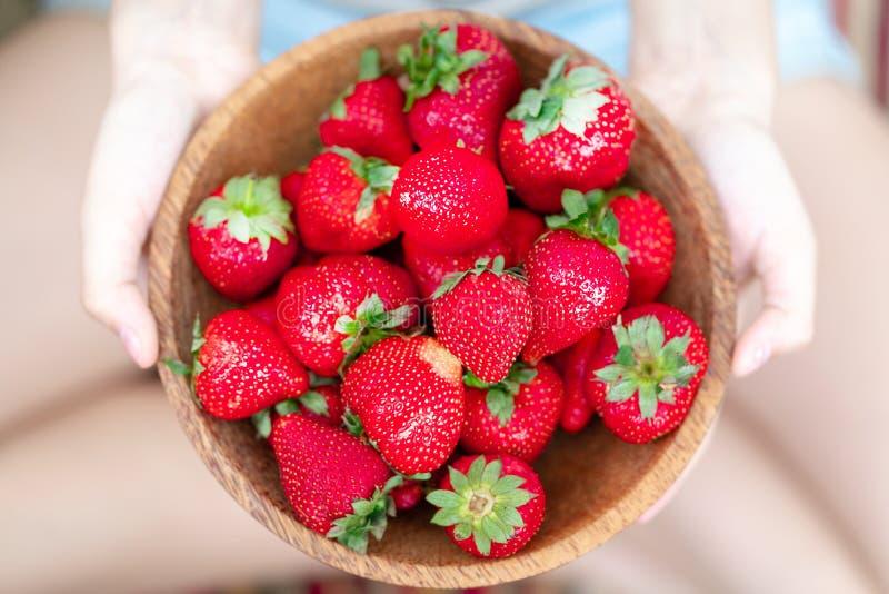 Houten plaat met aardbeien in meisjeshand op lichte achtergrond stock afbeelding