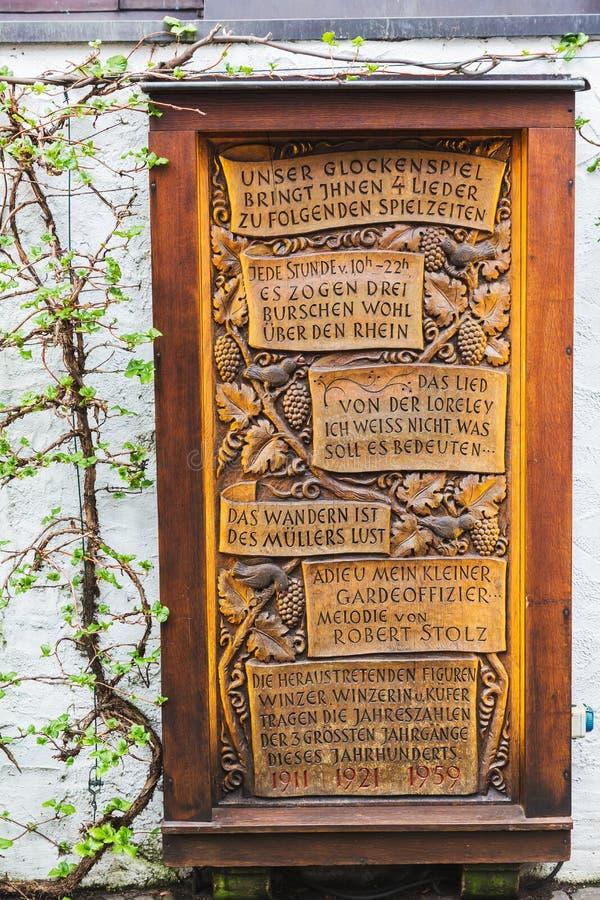 Houten plaat met gegraveerde berichten aan lyrische gedichten van een klokkengelui bij een muur in Ruedesheim am Rijn, Duitsland stock foto
