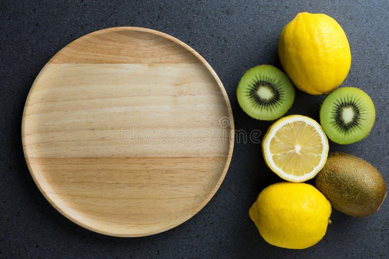 Houten plaat met kiwi en citroen De hoogste vlakke mening, legt stock foto's