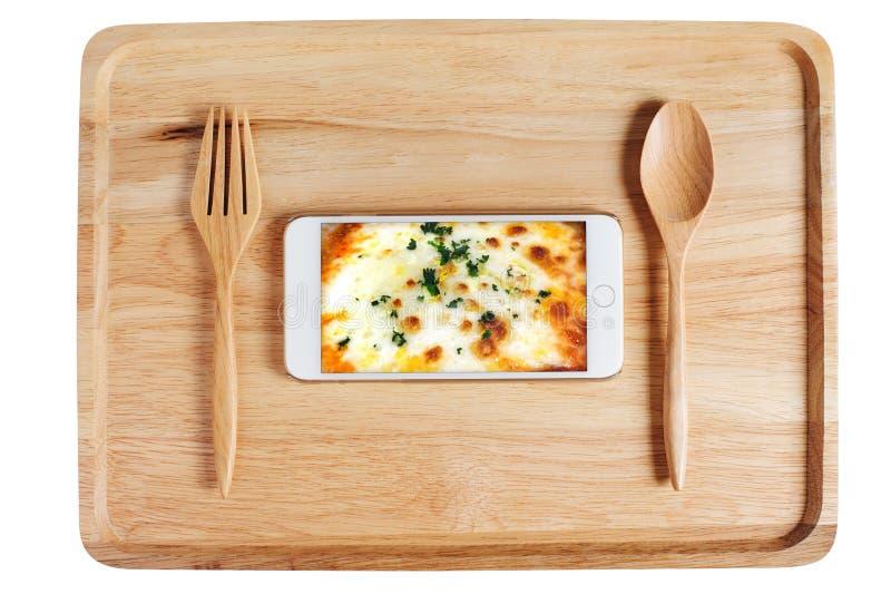 Houten plaat met lepelvork en celtelefoon die voedsel op morn tonen royalty-vrije stock fotografie