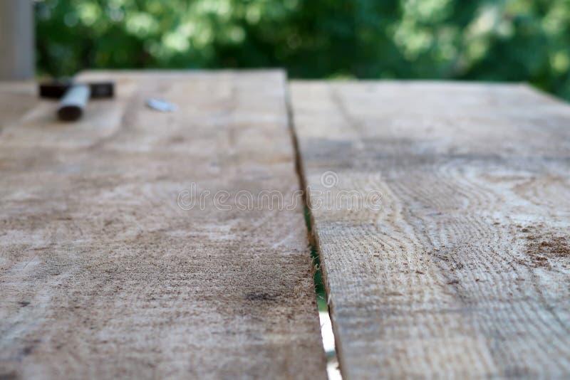 Houten plank met een stapel van spijkers en hamer op vage achtergrond stock foto's