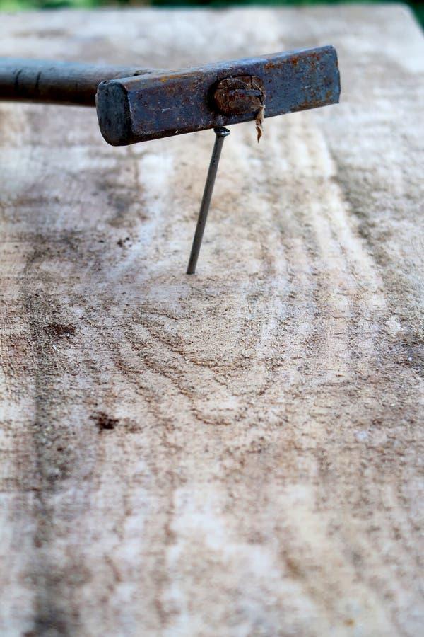 Houten plank met spijker en hamer in nadruk royalty-vrije stock afbeeldingen