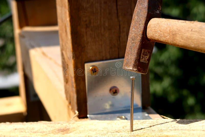 Houten planken en polen met spijker, schroeven en hamer in nadruk op een bouwwerf stock afbeelding