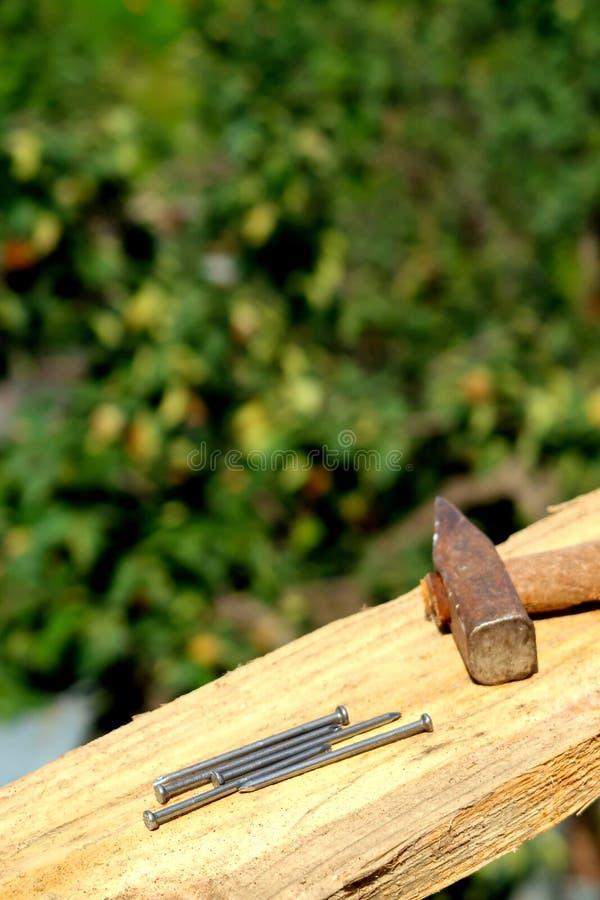 Houten planken met spijkers en hamer in nadruk op een bouwwerf stock foto