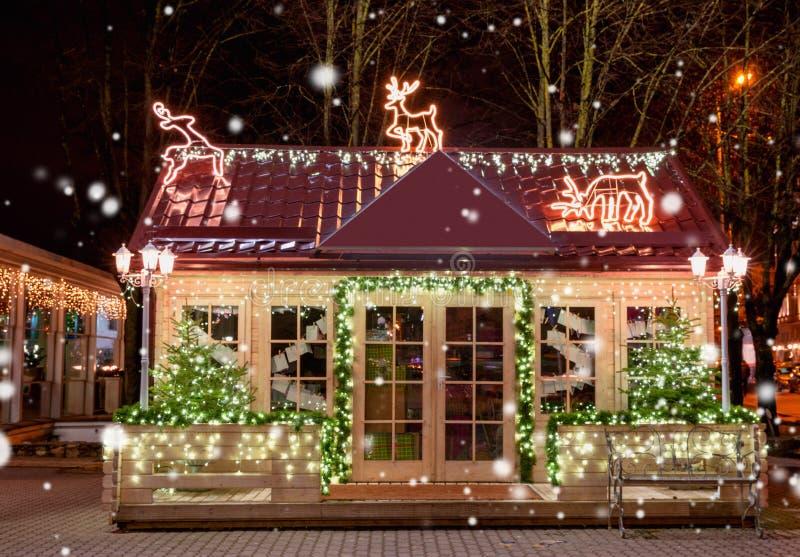 Houten plattelandshuisje met Nieuwjaardecoratie in de nacht De achtergrond van Kerstmis Het venster van Kerstmis Kerstboom buiten stock fotografie