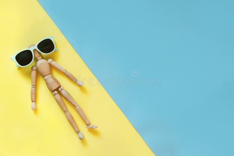Houten pop met zonnebril op geel als zandstrand en blauw als water Conceptentan en strand Gevaar van zonnebrand Uvprotec stock fotografie
