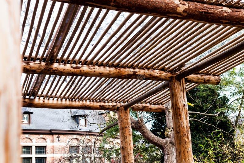 Houten portiek onder een grote boom Houtconstructie en bouwconstructie Met de hand gemaakte houten structuren stock foto