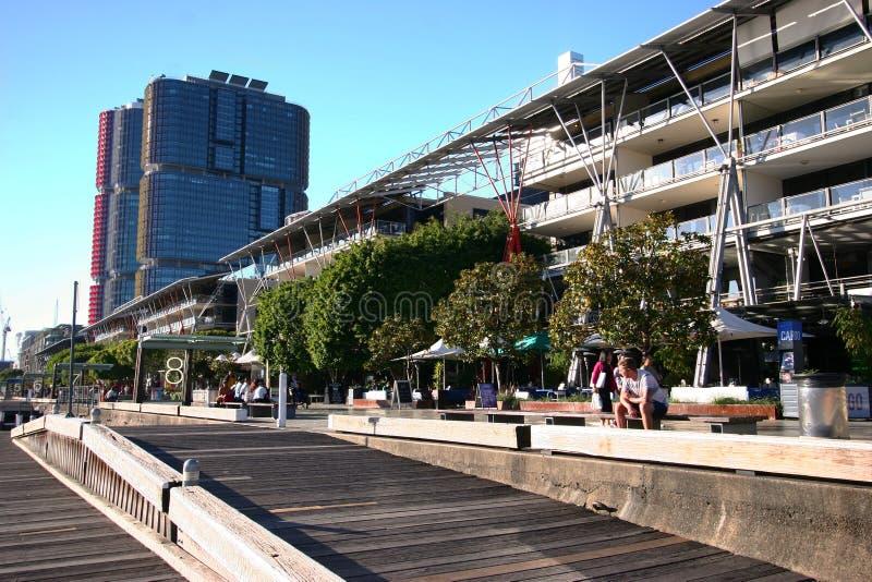 Houten promenade en hellingen met banken en bomen in Barangaroo, Sydney, Australië, met iconische stedelijke horizon van glaswolk royalty-vrije stock foto's
