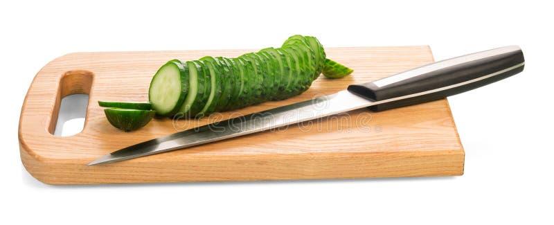 Houten raad met gesneden komkommer, mes op wit stock fotografie