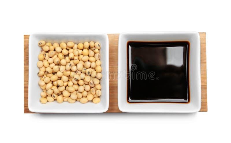 Houten raad met schotels van sojasaus en bonen op witte achtergrond royalty-vrije stock afbeeldingen