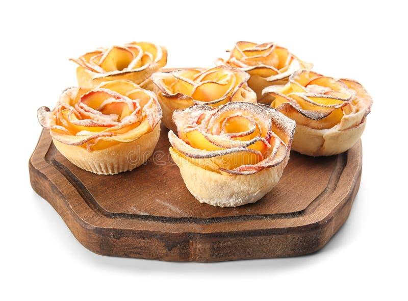 Houten raad met smakelijke appelrozen van bladerdeeg op witte achtergrond stock fotografie