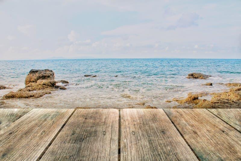 Houten raad op rotsstrand en blauwe overzees stock afbeelding