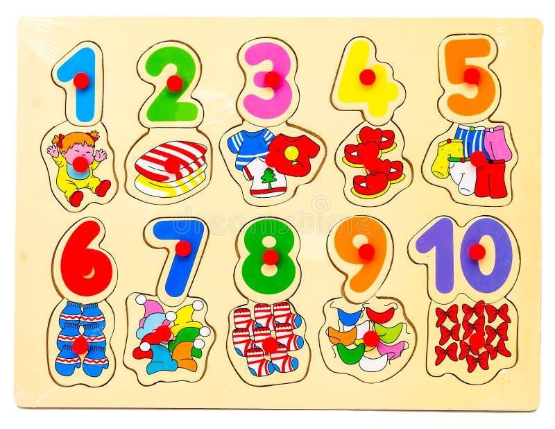 Houten raadsel met aantallen en rekenkundige tekens met beelden van punten De hand van kinderen neemt de cijfers van royalty-vrije stock afbeeldingen