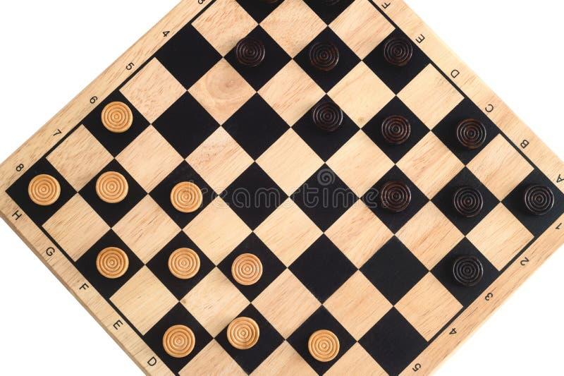 Houten schaakbord met uit elkaar geplaatst die controleurs op wit worden geïsoleerd royalty-vrije stock afbeeldingen
