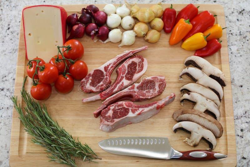 Houten scherpe raad in keukenlijst met het ruwe rode vlees, de rozemarijn, de paddestoelen, de tomaten, de kaas, de uien en de pe royalty-vrije stock fotografie