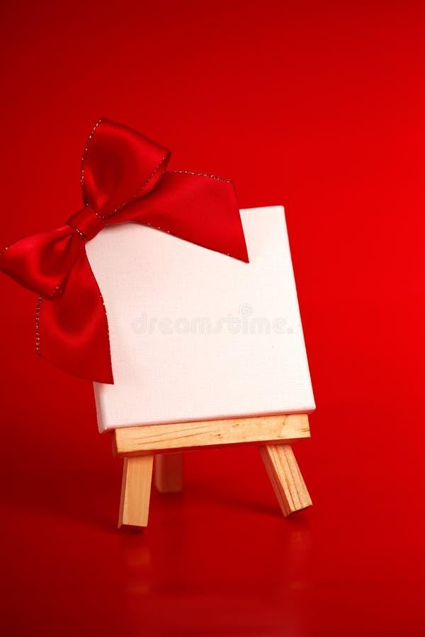 Houten schildersezel met leeg canvas op rode achtergrond royalty-vrije stock foto's