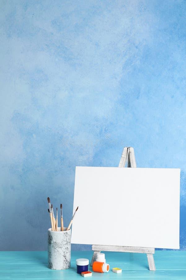 Houten schildersezel met lege canvas raad en het schilderen hulpmiddelen voor kinderen op lijst royalty-vrije illustratie