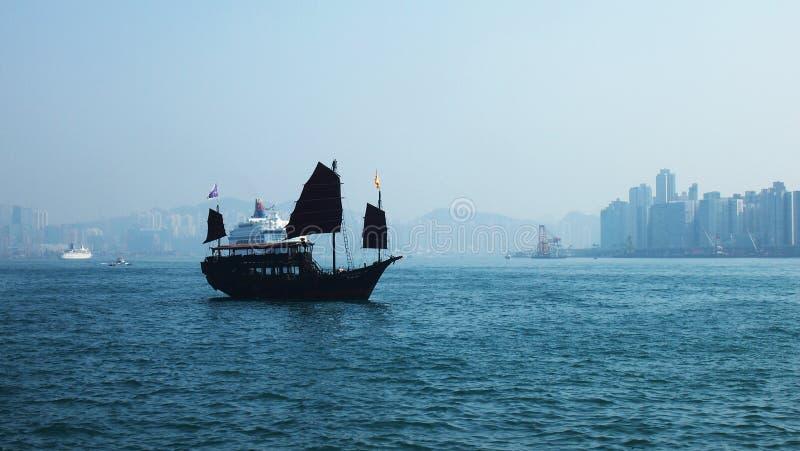 Houten schip in Hong Kong Harbor Skyline stock afbeelding