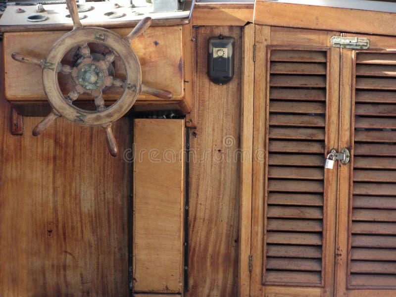 Houten schipdek met roer en navigatieinstrumenten Bijzondere mening van een retro stuurwiel van een oud varend schip royalty-vrije stock fotografie