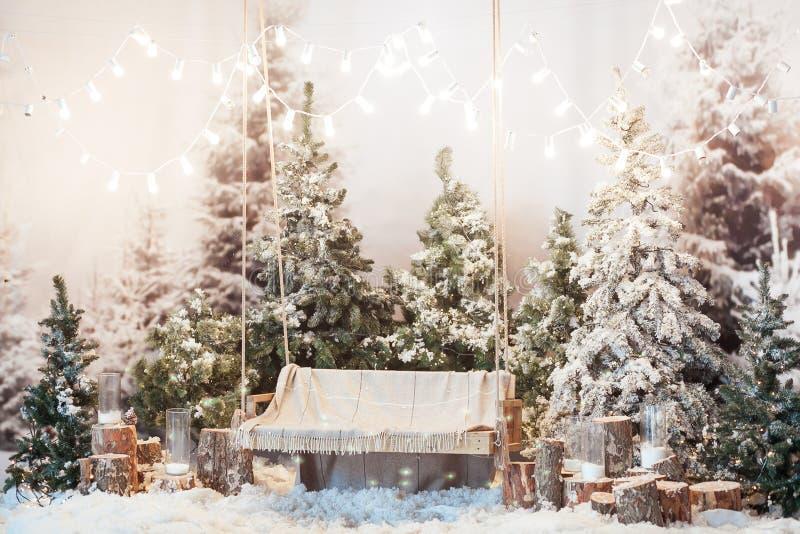 Houten schommeling in een snow-covered park of een bos met nette bomen en stompen, grote kaarsen in glasvazen, terwijl het sneeuw royalty-vrije stock foto