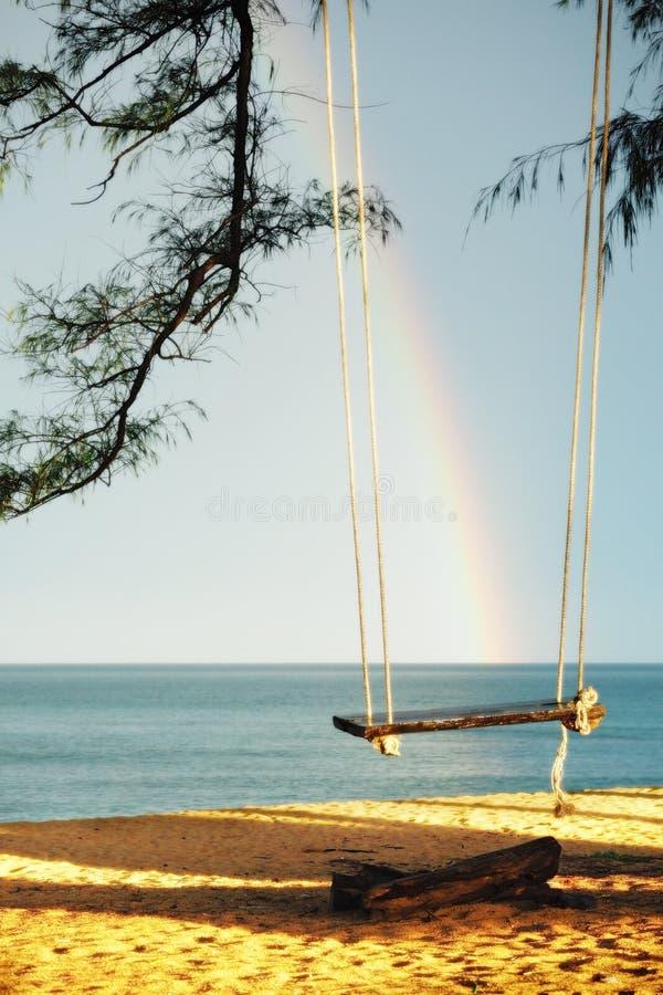 Houten schommeling naast het overzees met de achtergrond van de regenbooghemel stock afbeelding